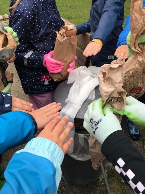 Kinderhände sammeln Müll ein bei der renaturierten Würm in Allach.